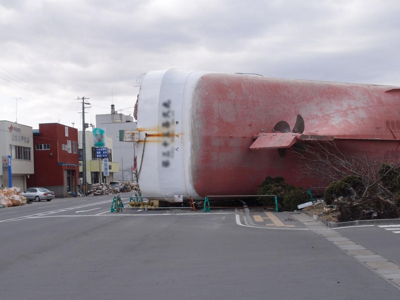 「日常に食い込んだ非日常」車道に巨大な船が横たわる。