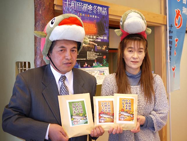 新商品の「十和田湖ひめますカレー」「十和田湖ひめますシチュウ」「十和田湖ひめますご飯の素」と開発者の伝法良輔さん